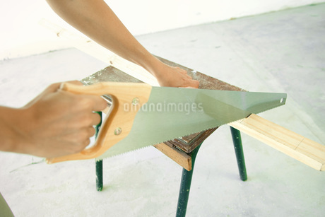 Woman sawing piece of wood of handsの写真素材 [FYI04319110]