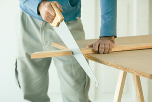 Man sawing piece of woodの写真素材 [FYI04319115]
