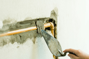 Applying plaster over pipe in wallの写真素材 [FYI04319116]