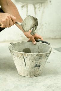 Man holding trowel over bucket of handsの写真素材 [FYI04319127]