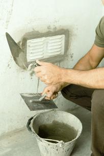 Man applying putty around air ventの写真素材 [FYI04319128]