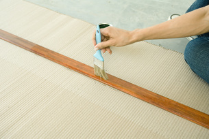 Woman staining piece of wood of armの写真素材 [FYI04319130]