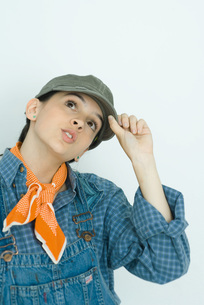 Teenage girl adjusting cap, looking upの写真素材 [FYI04319165]