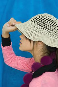 Teenage girl pulling sun hat over eyesの写真素材 [FYI04319173]