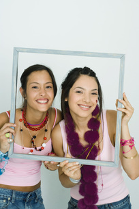 Two friends holding up frame togetherの写真素材 [FYI04319179]
