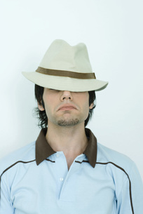 Young man wearing hat, eyes coveredの写真素材 [FYI04319199]