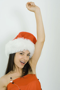 Woman wearing Santa hat, arm raisedの写真素材 [FYI04319215]