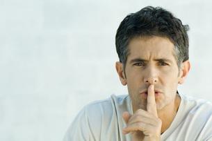 Mature man holding finger over lipsの写真素材 [FYI04319227]