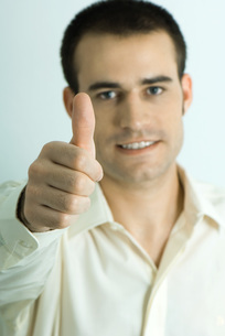 Man looking, giving thumbs up signの写真素材 [FYI04319245]