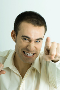 Man making face and pointing at cameraの写真素材 [FYI04319248]