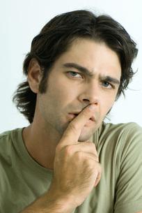 Man holding finger over lipsの写真素材 [FYI04319261]
