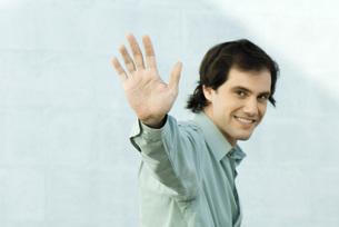 Man waving at camera, smilingの写真素材 [FYI04319271]