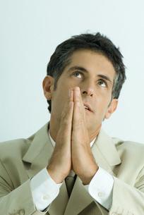 Businessman praying, looking upの写真素材 [FYI04319272]
