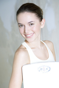 Woman holding bathroom scale at cameraの写真素材 [FYI04319296]