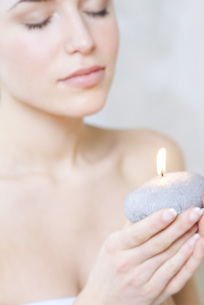 Young woman holding candle, eyes closedの写真素材 [FYI04319308]