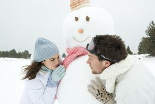 Couple looking around snowmanの写真素材 [FYI04319353]