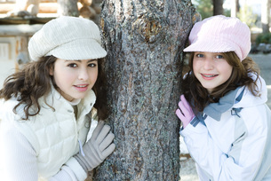 Two friends leaning against tree trunkの写真素材 [FYI04319356]
