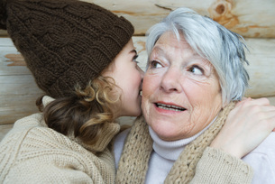 girl whispering into grandmother's earの写真素材 [FYI04319392]
