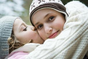 Sister kissing girl on cheekの写真素材 [FYI04319398]
