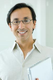 Man smiling, holding laptop computerの写真素材 [FYI04319406]