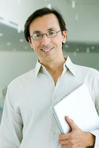 Man smiling, holding laptop computerの写真素材 [FYI04319422]