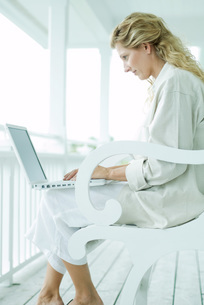 Woman sitting and using laptop computerの写真素材 [FYI04319443]