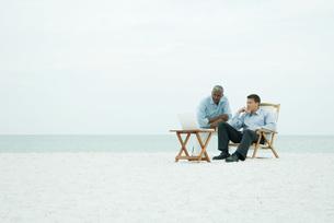 Two men looking at laptop computerの写真素材 [FYI04319445]