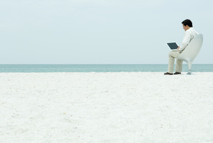 Man using laptop computer at the beachの写真素材 [FYI04319448]