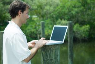 Man using laptop computer outdoorsの写真素材 [FYI04319449]