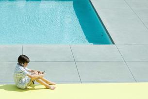 Boy sitting next to swimming poolの写真素材 [FYI04319455]