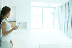 Woman standing, looking at cell phoneの写真素材 [FYI04319457]