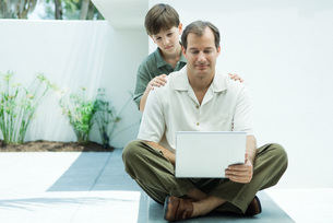 Man using laptop computer, son lookingの写真素材 [FYI04319458]
