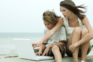 Girl and brother using laptop computerの写真素材 [FYI04319464]