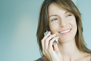 Woman using cell phone, smilingの写真素材 [FYI04319469]