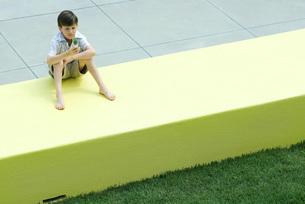 Boy sitting on low wallの写真素材 [FYI04319470]
