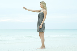 Woman photographing self with cell phoneの写真素材 [FYI04319471]