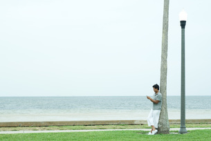 Man leaning against tree trunkの写真素材 [FYI04319474]