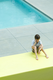 Boy sitting in front of swimming poolの写真素材 [FYI04319475]