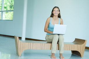 Girl sitting and using laptop computerの写真素材 [FYI04319476]