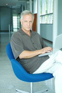 Man sitting and using laptop computerの写真素材 [FYI04319477]