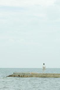 Man standing on pier, carrying laptopの写真素材 [FYI04319480]