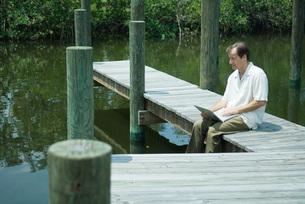 Man sitting and using laptop computerの写真素材 [FYI04319485]