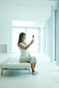Woman photographing self with cell phoneの写真素材 [FYI04319487]