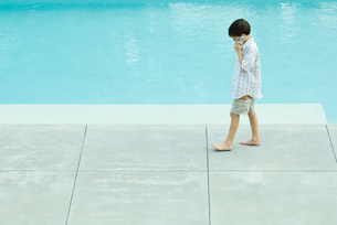 Boy walking next to swimming poolの写真素材 [FYI04319495]