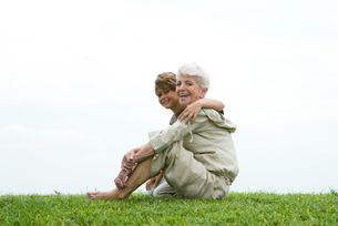 Woman and grandson sitting on grassの写真素材 [FYI04319499]