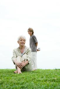 Woman sitting on grassの写真素材 [FYI04319501]