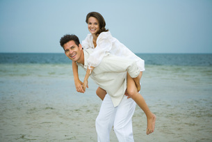 Man carrying female companion piggybackの写真素材 [FYI04319519]