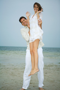 On beach, man holding Girl up in airの写真素材 [FYI04319520]