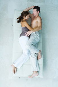 Couple lying on chaise longue togetherの写真素材 [FYI04319548]