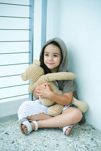 Girl sitting and holding teddy bearの写真素材 [FYI04319556]
